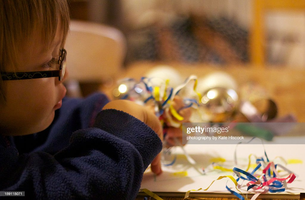 Small child making a picture with shredded paper : Stock Photo