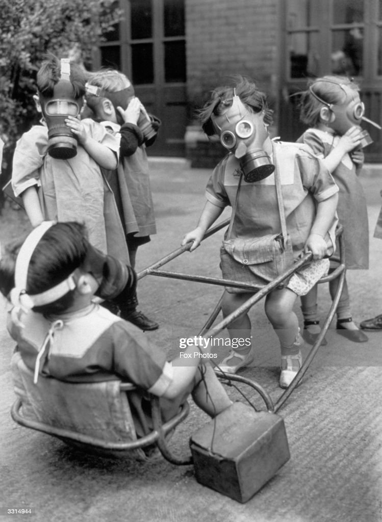 Small children in a playground wearing their gas masks.