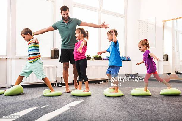 Small children walking on Pilates balls on training class.