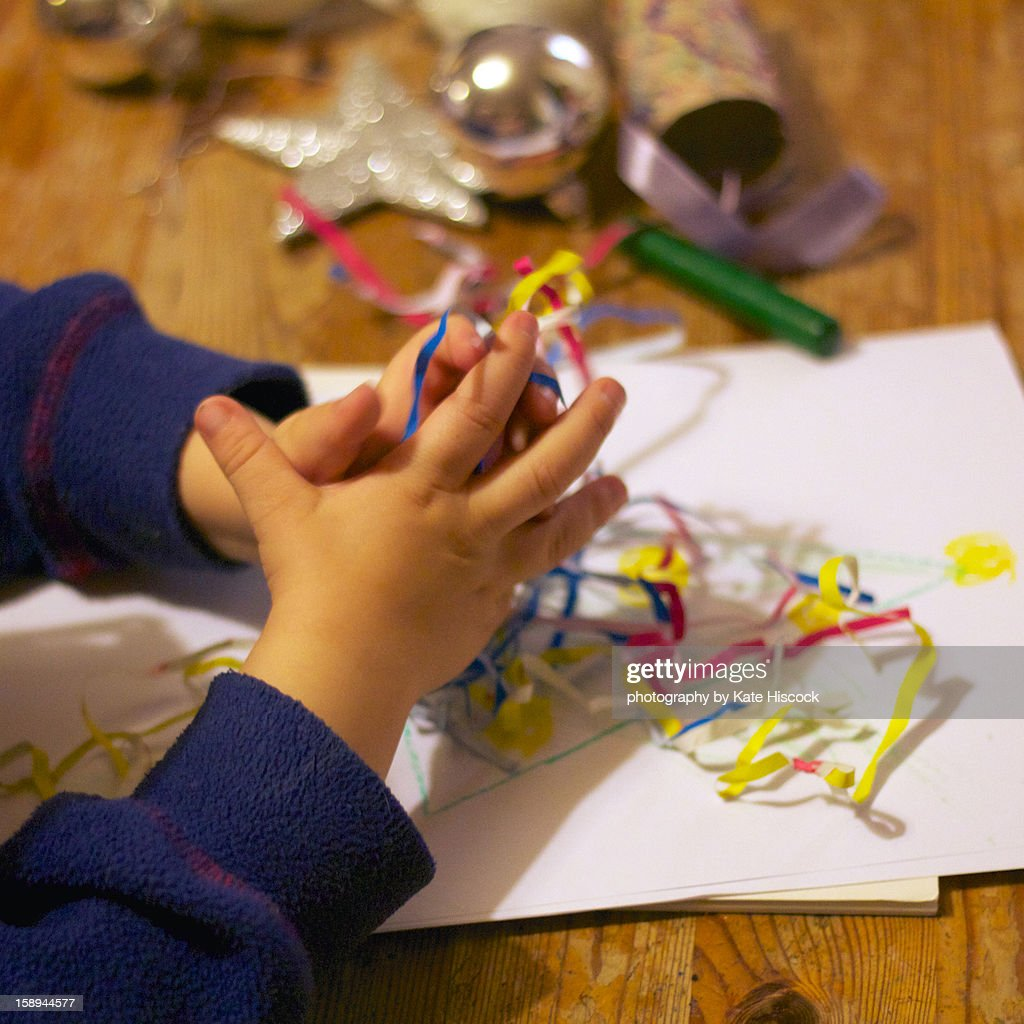 A small child's hands doing Christmas crafts : Stock Photo