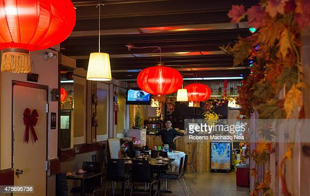 Small Chinese restaurant with glowing Chinese lanterns and waiter behind the far table holding his arms open picture taken at a downward angle to...