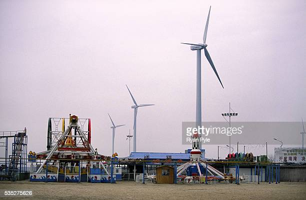 A small circus sits on an artificial beach as a wind turbine spins at the Fengxian Wind Farm site in Shanghai China China home to 16 of the worlds 20...