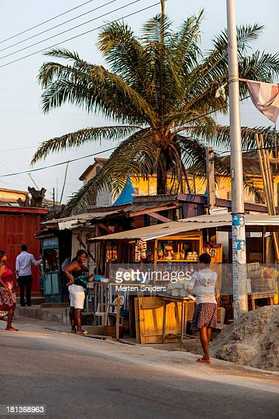 Small convenience store below a palm tree