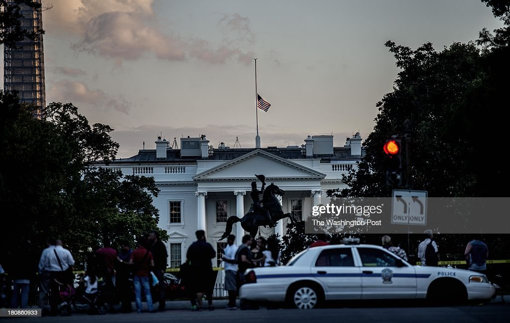 A small crowd gathers as police officers block the entrance to Lafayette Park and the White House grounds after officials tackled a man who threw a firecracker over the White House fence, on Monday September 16, 2013. The lowered flag to half staff atop the White House is in remembrance of those killed in today's shootings at the Navy Yard.