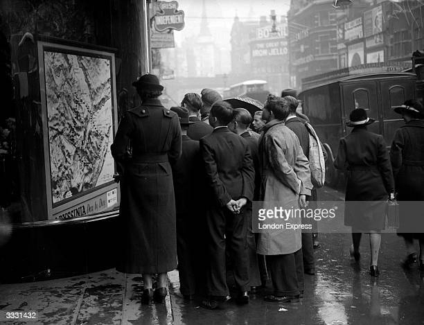 A small crowd in Fleet Street London looking at a map of Abyssinia now Ethiopia in the window of the Express building around the time of the Italian...