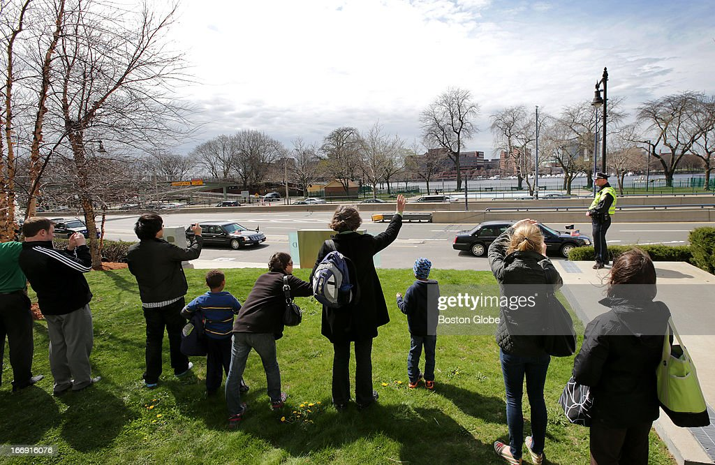 A small crowd of onlookers wave as President Obama's motorcade departs Mass. General Hospital after the president stopped to visit the victims of the Boston Marathon bombings.