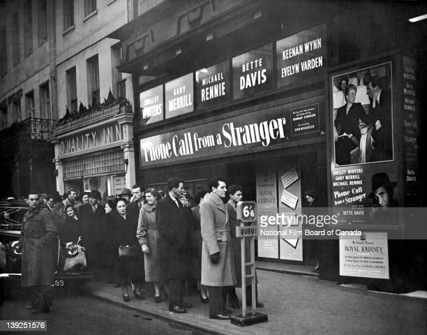 A small crowd waits in line in front of the Odeon Theatre in Leicester Square where the NFB film 'Royal Journey' is being shown London England 1952...