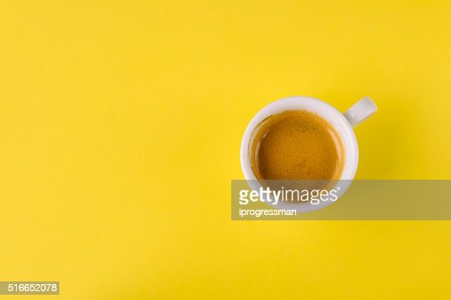 Small cup of coffee on bright yellow background : Stock Photo