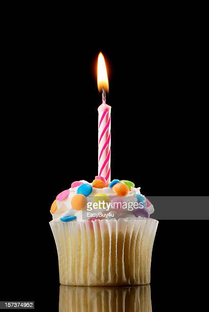 Small cupcake with colorful candy and a candle on top
