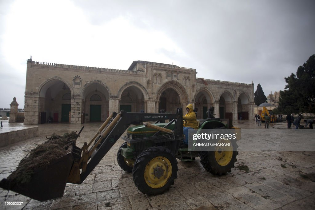 A small digger removes dirt following an overnight storm from the grounds of the Al-Aqsa Mosque compound, in Jerusalem's old city, on January 7, 2013. Stormy weather, including high winds and heavy rainfall, lashed Israel and the Palestinian territories, downing powerlines and trees and causing several injuries.