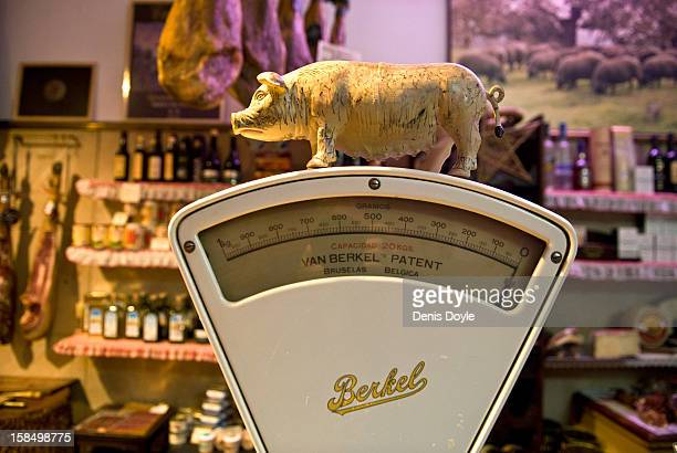A small figurine of an Iberian Pig sits on an old weighing scales at the Alberto Lopez Araque jamon Iberico shop on December 14 2012 in Madrid Spain...