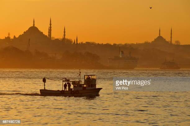 A small fishing boat sails up from the Sea of Marmara into the Bosphorus at sunset with the skyline of Istanbul's Old City as a backdrop