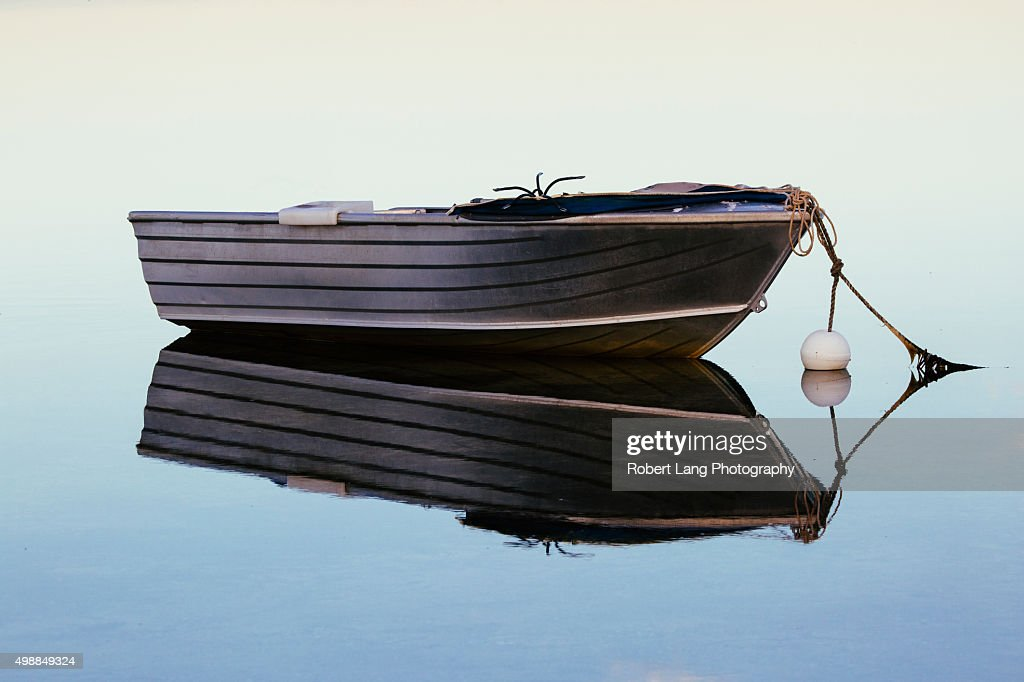 Small fishing boat with reflection in water stock foto for A small fishing boat