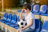 Small football fan disappointed after the loss goal by his favorite team