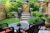 Small townhouse garden with patio furniture amidst blooming lavender.