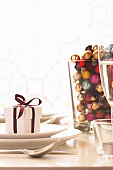 Small gift box on plate and glass vase filled with baubles