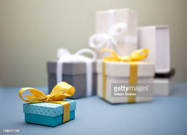 Small gift box with yellow bow, gifts behind it
