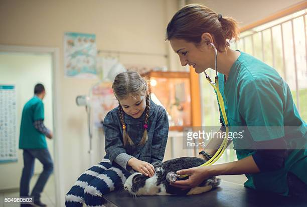 Small girl brought her pet on medical exam at vet's.