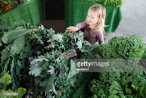 Small girl buying vegetables