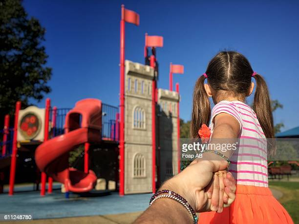 Small girl dragging her mother to the playground