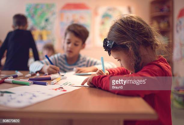 Small girl drawing on a class in a preschool.