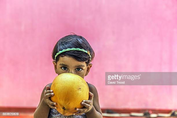 Small girl drinking from a coconut