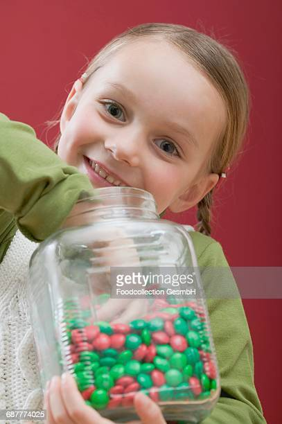 Small girl eating chocolate beans out of sweet jar