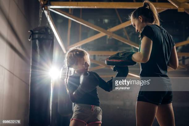 Small girl having a boxing training with her coach in a gym.