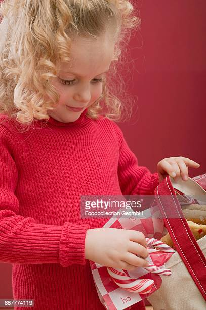 Small girl holding bag of candy canes and biscuits