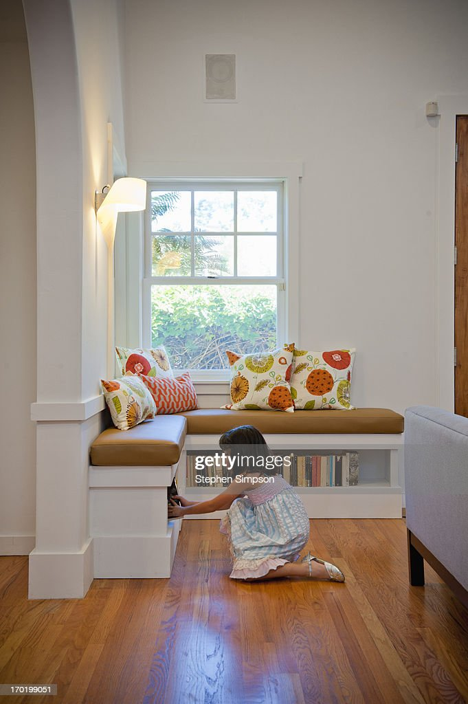 small girl in living room with books : Stock Photo