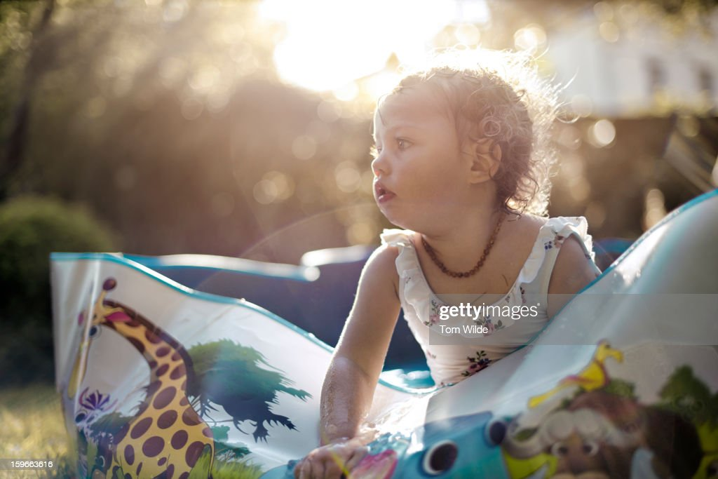 Small girl in paddling pool with sun behind her : Stock Photo