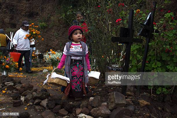 A small girl is carrying offerings for her dead in the local cemetery of Janitzio on November 1 2015