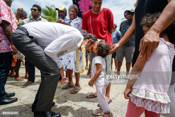 TOPSHOT A small girl kisses French Prime Minister Edouard Philippe on the forehead as he bends down to greet her in the town of We on Lifou Island on...