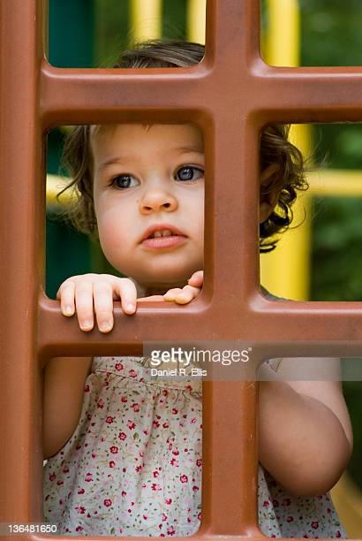 Small girl looking through window