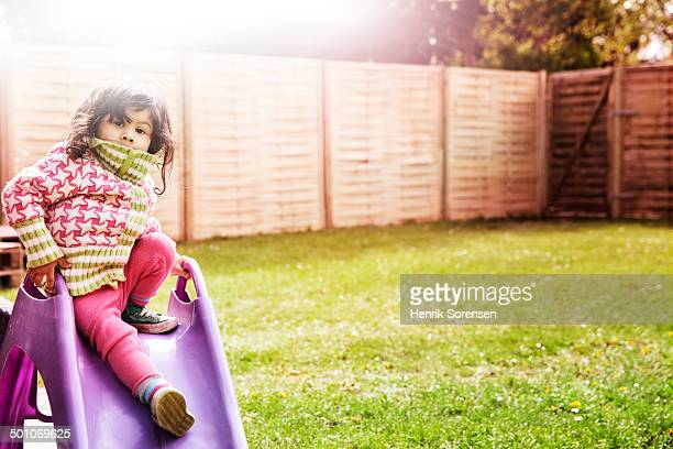 small girl on slide in garden
