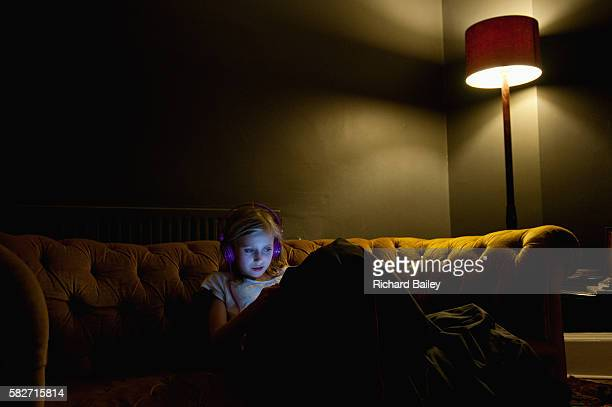 Small girl on sofa looking at a tablet.