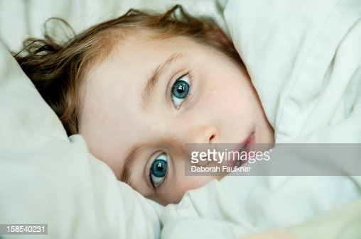 Small girl peeping through bed covers   Stock Photo. Small Girl Peeping Through Bed Covers Stock Photo   Getty Images