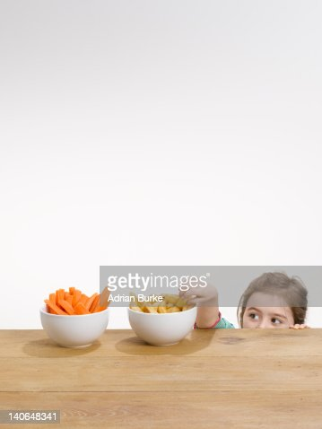 Small girl pinching chips from a bowl : Stock Photo