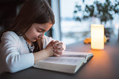 A small girl with bible at home, praying.