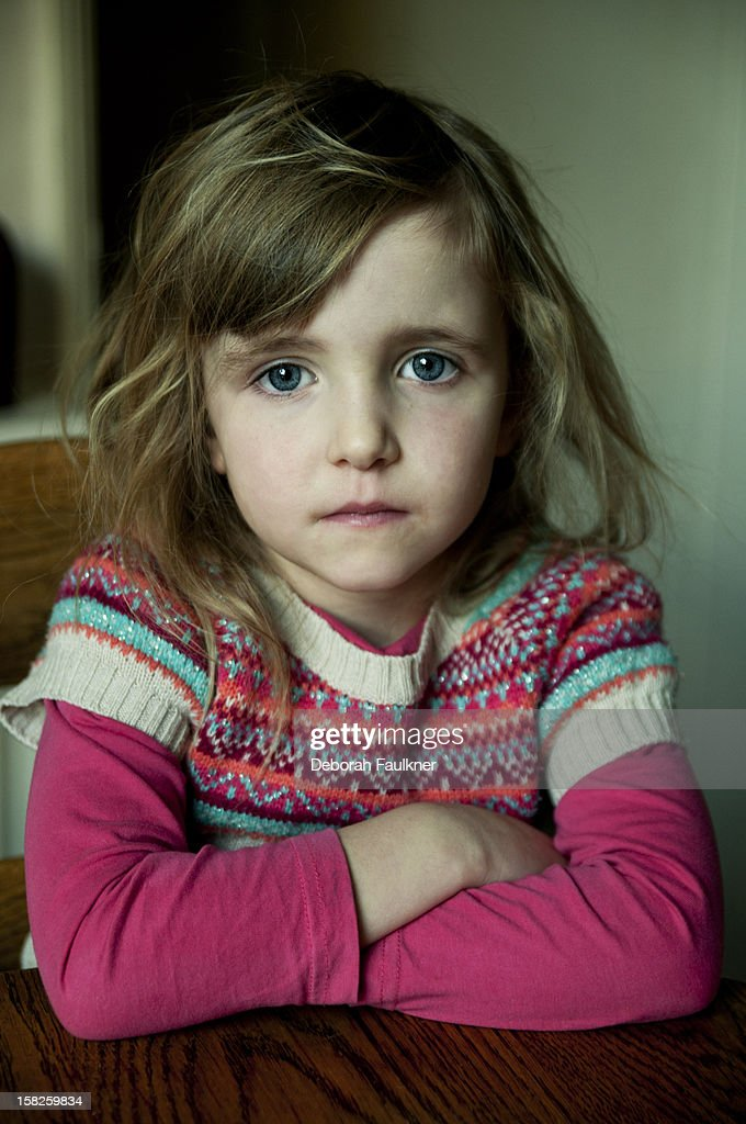 Small girl sat at table with arms folded : Stock Photo