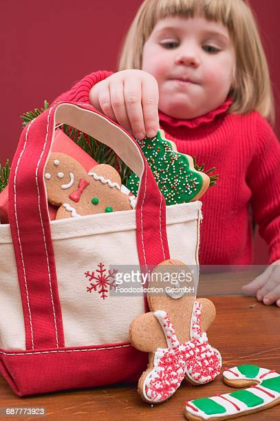 Small girl taking Christmas biscuit out of bag
