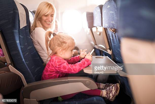 Small girl using smart phone while traveling with her mother.