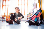 A small girl with a schoolbag at school, putting on shoes.