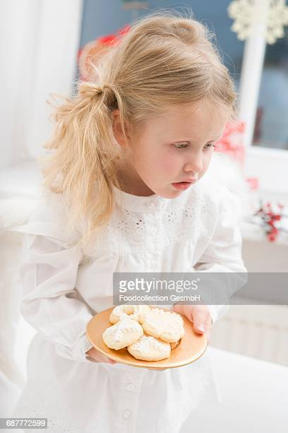 Small girl with angels wings holding plate of biscuits