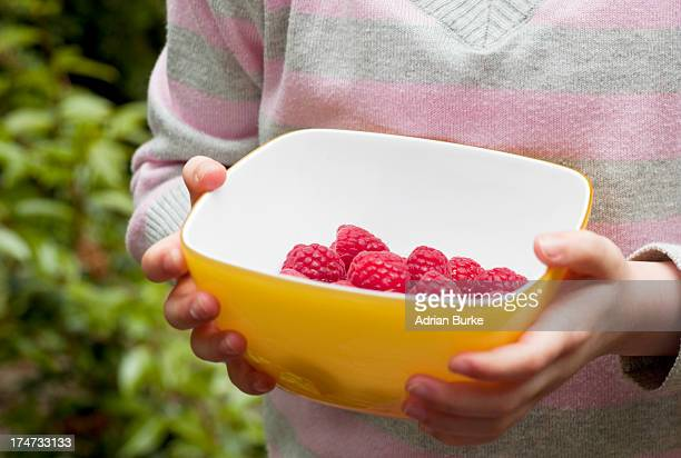 Small girl with bowl of Raspberries.