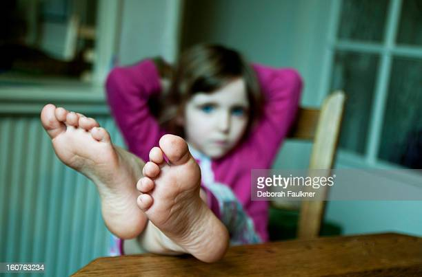 Small girl with feet on table