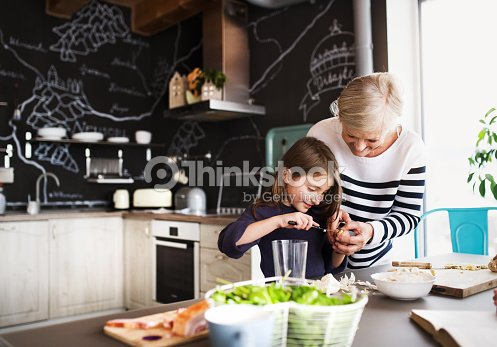 A small girl with grandmother cooking at home. : Stock Photo