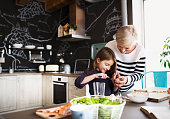 A small girl with her grandmother at home, cooking. Family and generations concept.