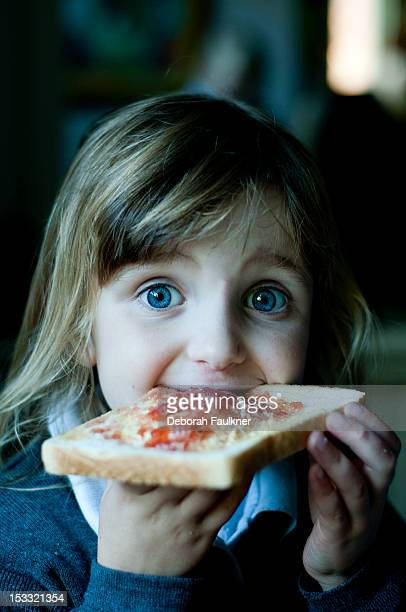 Small girl with jam on toast