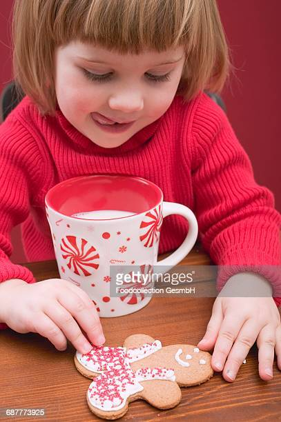 Small girl with mug of milk and gingerbread man